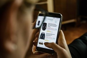 A customer scrolling positive ratings on a mobile device while choosing a dress.